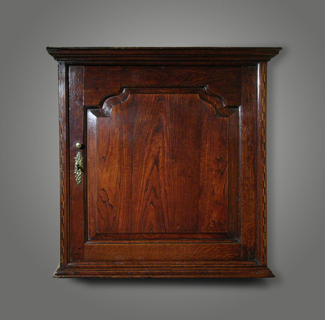 Welsh oak wall-hanging cupboard of particularly fine quality, with a shaped  raised-and-fielded panel door flanked by strips of chequer inlay, the  interior ... - ANTIQUE WALL CUPBOARD With Inlaid Decoration And Interior Drawers