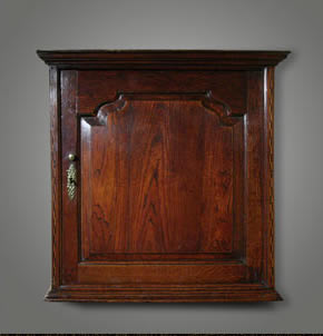 oak wall-hanging cupboard of particularly fine quality, with a shaped raised-and-fielded panel door flanked by strips of chequer inlay, the interior has replaced backboards and is fitted with small spice drawers