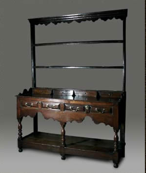 Welsh oak dresser, the low open rack with shaped frieze raised on elaborately shaped shoes and a row of spice drawers