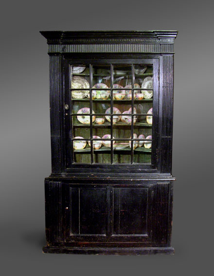 Antique Welsh two section corner cupboard from Pembrokeshire, circa 1790. This formerly built-in cupboard has a very intricately embellished cornice with a reeded frieze below. The top section has an inverted breakfront and a single door with square glazing bars framed on both sides by a narrow applied moulded panel. The base has a double-panelled door with an applied moulded panel either side. The whole is supported on a plinth