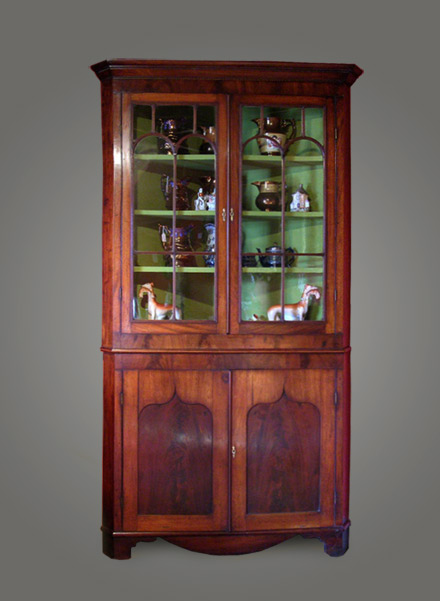 Antique Mahogany two-section corner cupboard from Llanelli/Swansea area, circa 1840. The top section of this corner cupboard has a neat cornice that sits above a wide strip of cross-banding with chequerwork stringing, with two glass doors with reeded glazing bars and a painted shelved interior section