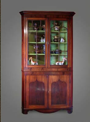 Mahogany two-section corner cupboard, the upper section with fluted arched glazing bars