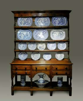 antique dresser, with an open plate rack with shaped sides and shoes above a base with three drawers