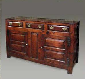 Oak cupboard with three drawers above a pair of doors with double fielded panel doors