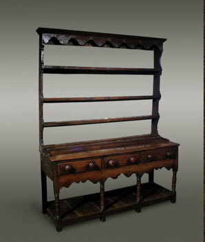 Welsh oak dresser, the open rack with shaped frieze and sides over a base of three drawers