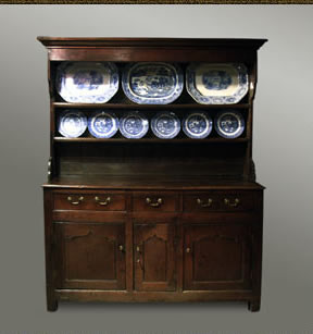 Welsh  dresser, with an open overhanging plate rack with shaped sides above a base with three drawers over three cupboard doors
