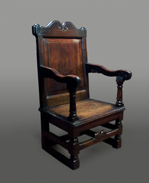 Welsh oak armchair, with a shaped apron and carved crest rail above a yew-wood raised and fielded panel, with shaped arms raised on turned supports