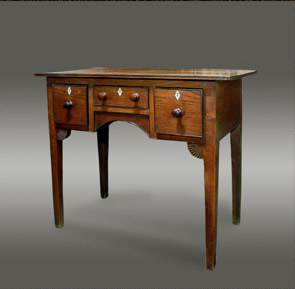 Welsh oak lowboy, the top with edge stringing above a central cock-beaded drawer flanked by square drawers over a central arch, raised on square tapered legs with sunburst corner spandrels, with bog oak embellishment